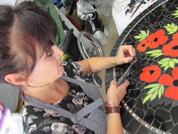 Pascale, mosaïste à Péret, travaille une mosaïque de faïence mate et brillante entourée de miroirs cassés à la main
