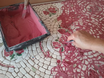 Application du joint, pigment à la chaux, pour une mosaïque en assiette ancienne effectuée par Pascale Villegas mosaïste à Péret